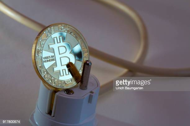 Symbol photo on the topic of high electricity consumption in international digital currency trading The picture shows a Bitcoin and a power plug with...