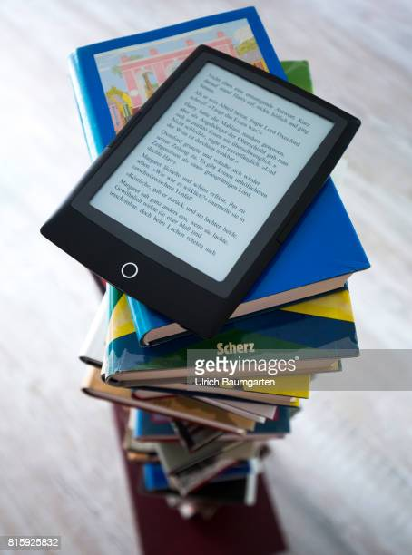 Symbol photo on the topics of literature reading eBook books leisure vacation etc The photo shows an eBook on stacked books