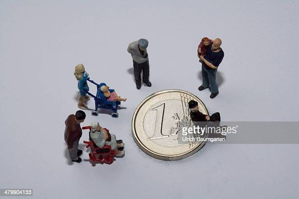 Symbol photo on the topics of poverty subsistence minimum wage oldage poverty and child povertyMiniatur figures standing and sitting on a 1 Euro...