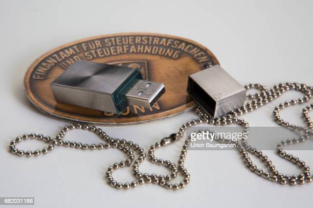 Symbol photo on the topics tax evasion, tax investigation, tax fraud, etc. The photo shows a USB stick on the badge of the tax office for criminal...