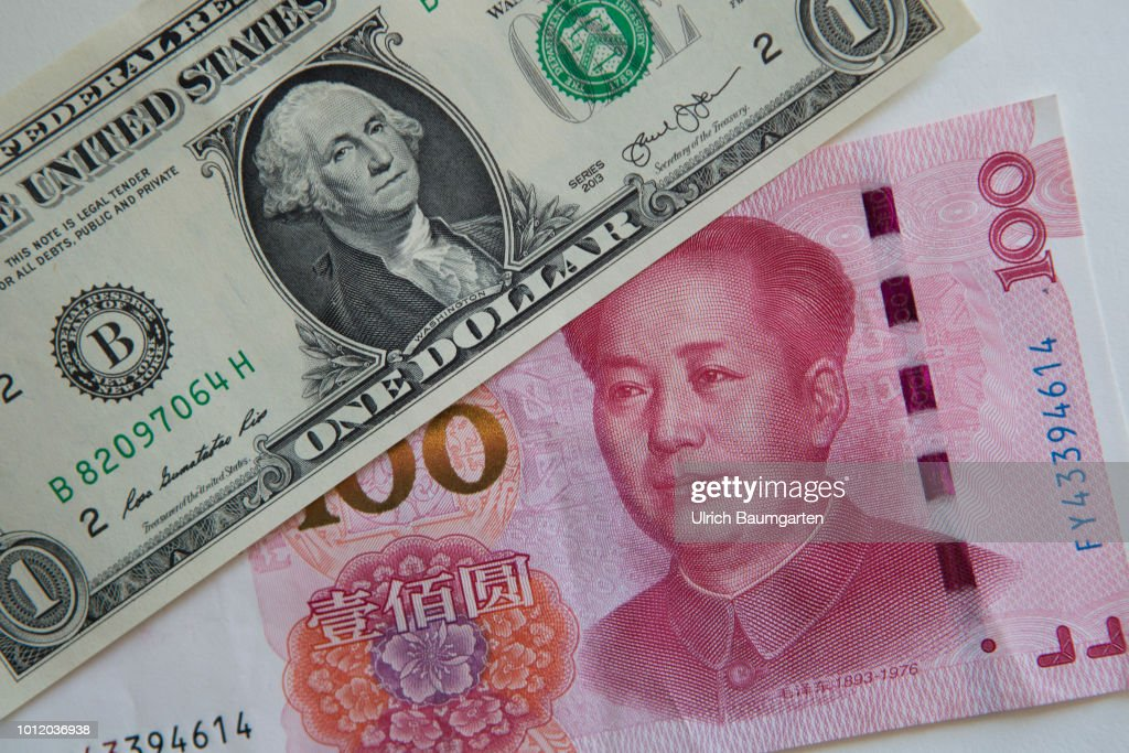 A one hundred yuan banknote and a one dollar banknote. : News Photo
