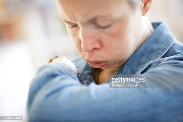 Symbol picture on the subject of the risk of infection A woman coughs in the crook of her arm on April 05 2020 in Berlin Germany In the context of...