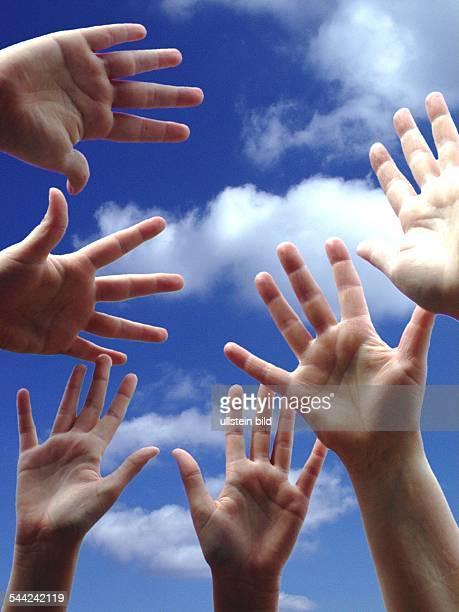 Symbolbild Zusammenhalten Familie Team Haende vor blauem Himmel