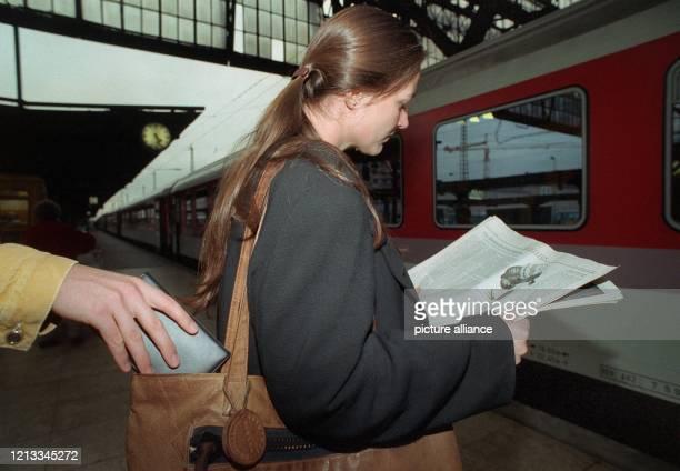 Diebstahl. Aufgenommen am 8.10.1992 im Frankfurter Hauptbahnhof. Gestellte Szene: Hand nimmt Brieftasche aus einer Handtasche, ohne das die Zeitung...