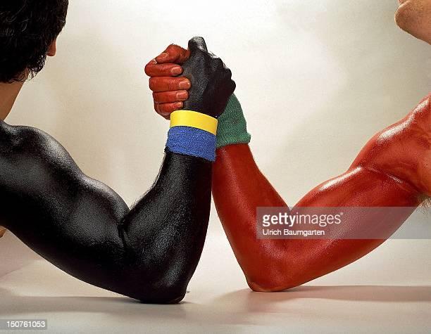 GERMANY BONN Symbolfoto zu den Themen Parteikonflikte Koalitionen Wahlkampf etc UBz schwarzen Arm mit blaugelbem Schweissband und roten Arm mit...