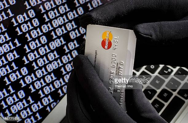 Symbolic feature with topic online crime data theft and credit card fraudsters here a closeup of a keyboard of a laptop with hands in black gloves...