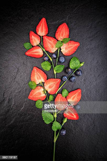 Symbolic flower shaped of sliced strawberries, melissa and blueberries on slate