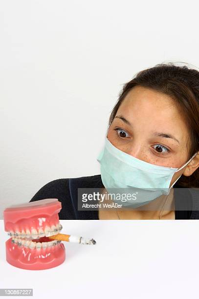 symbolic image for adolescent smokers, young woman looking in horror at dentures with fixed braces and a smoking cigarette - techniker stock pictures, royalty-free photos & images