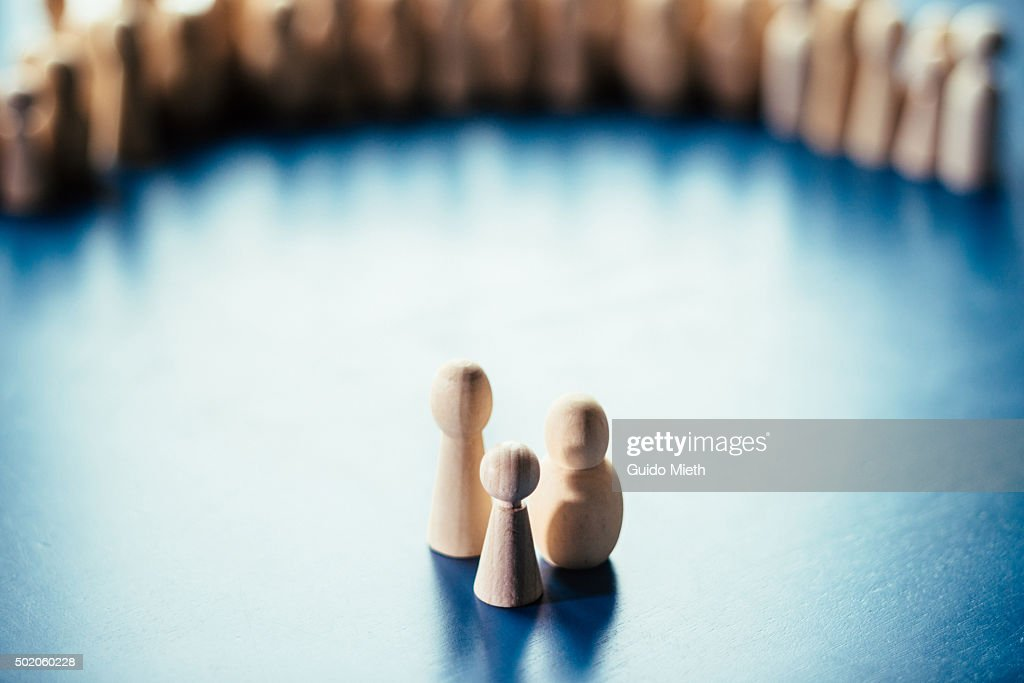 Symbolic pawn family in a circle of pawns. : Stock Photo