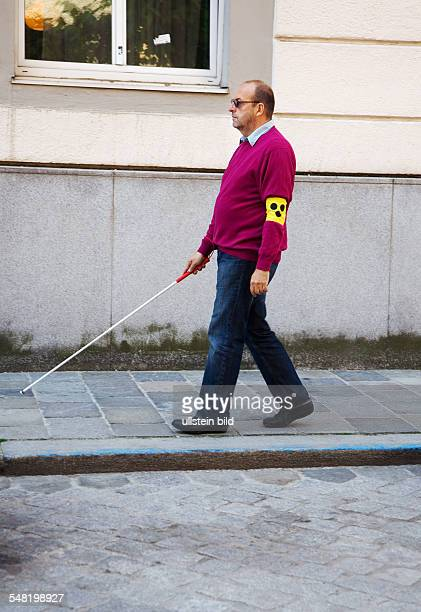 symbolic photo blind person blind man with blindman's stick on a pavement