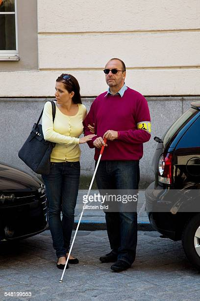 symbolic photo blind person young woman is accompanying a blind man