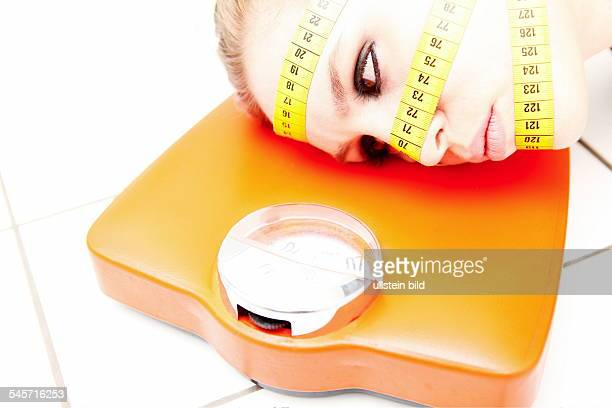 symbolic photo diet aesthetic surgery woman with measuring tapes on her face lying on scales