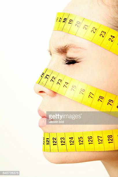 symbolic photo diet aesthetic surgery woman with measuring tapes on her face
