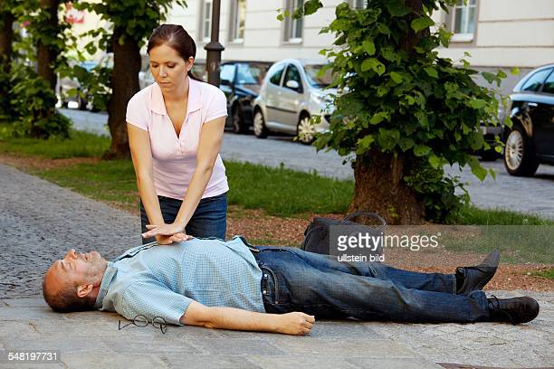 symbolic photo heart attack woman is giving first aid