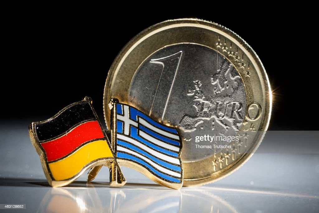 Symbolic photo of Greece and the Euro, one euro coin behind a badge with the national flags of Greece and Germany on February 10, 2015 in Berlin, Germany.