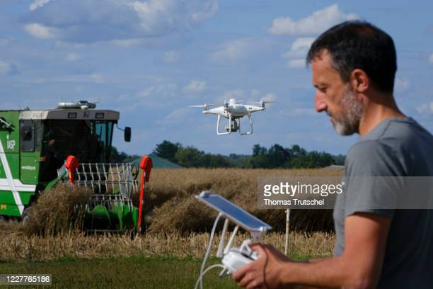 Symbolic photo on the subject of digitisation in agriculture. A drone flies in front of an autonomously driving plot combine harvester of the type...
