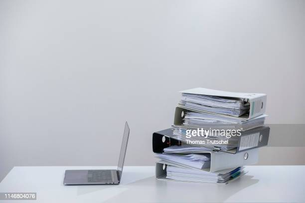 Symbolic photo on the subject of ' digitization in administration ' A computer is lying next to a pile of folders on May 29 2019 in Berlin Germany