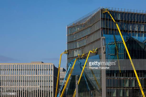 Symbolic photo on the subject of housing construction Construction workers assemble a glass facade on a skyscraper on a construction site on...