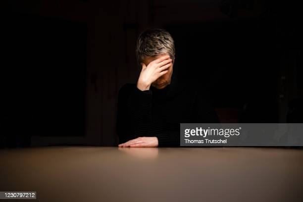 Symbolic photo on the subject of loneliness and depression: A woman sits alone at the table at night and holds her hands in front of her face on...