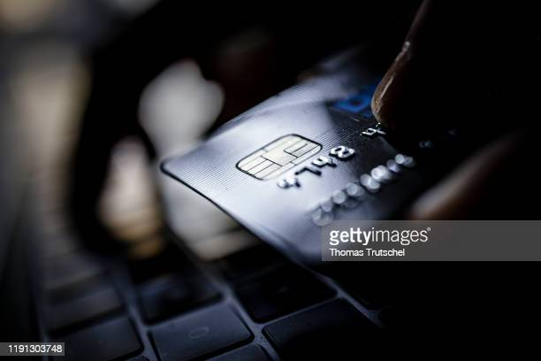 Symbolic photo on the subject of online shopping. A credit card is held next to the keyboard of a laptop.