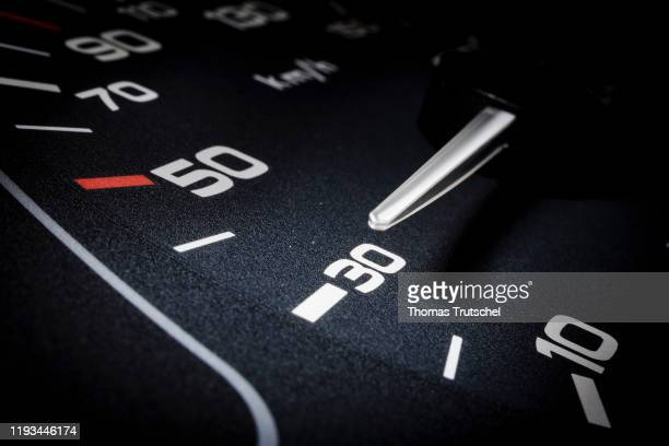 Symbolic photo on the subject of speed limit 30 km / h. A speedometer needle can be seen on a speedometer next to the display for 30 kilometers per...