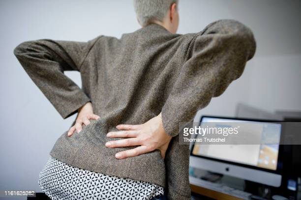 Symbolic photo on the topic of back pain A young woman sits in the office at the desk and takes hold of her back on August 14 2019 in Berlin Germany