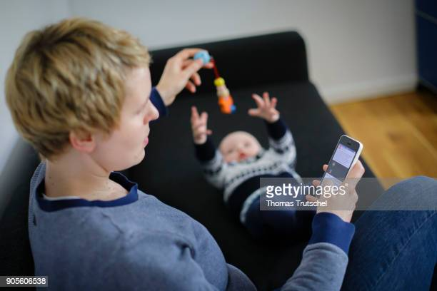 Symbolic photo on the topic of education A young mother looks at her smartphone while her child is playing on January 16 2018 in Berlin Germany