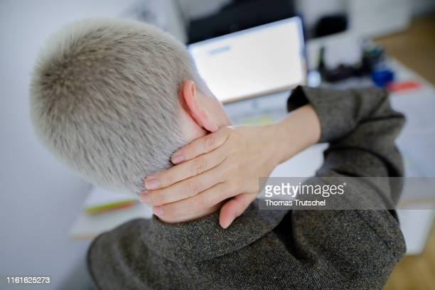 Symbolic photo on the topic of neck pain A young woman sits in the office at the desk and grabs her neck on August 14 2019 in Berlin Germany