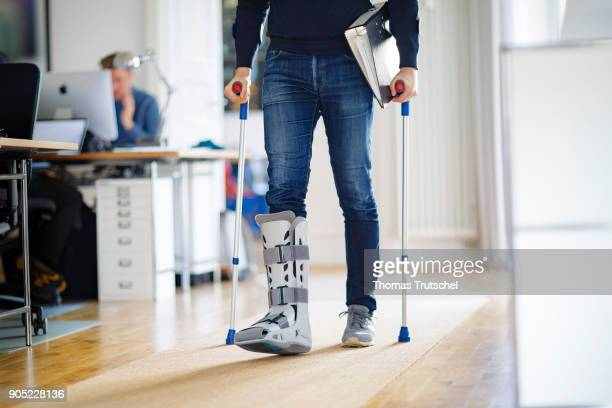 Symbolic photo on the topic Sick at work A man walks through a office with crutches and an orthosis on his leg on January 15 2018 in Berlin Germany