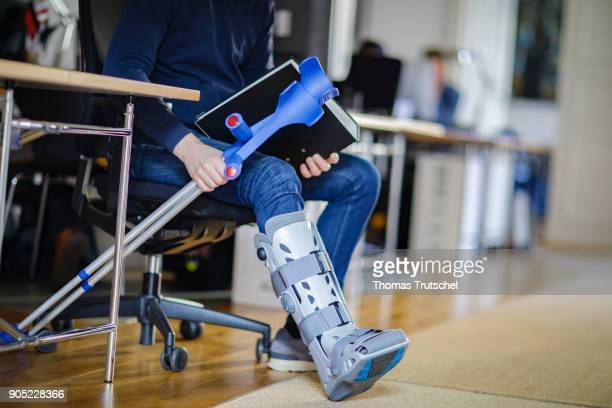 Symbolic photo on the topic Sick at work A man with crutches and an orthosis on his leg sitting at a desk in the office on January 15 2018 in Berlin...
