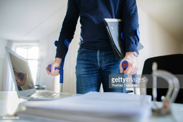 Symbolic photo on the topic Sick at work A man with crutches walks through a office on January 15 2018 in Berlin Germany