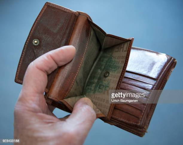 Symbolic photo on the topics poverty, old age poverty, bankrupt, pensioner poverty, broke, etc. The picture shows a hand with an empty money purse.