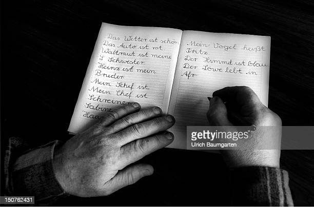 Symbolic photo to the topic Illiteracy Our picture shows Hands of a an elderly person are writing simple sentences