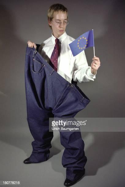 Symbolic photo to the topic 'Nothing fits together in Europa' Young man standing in an oversized jeans holding a European little flag