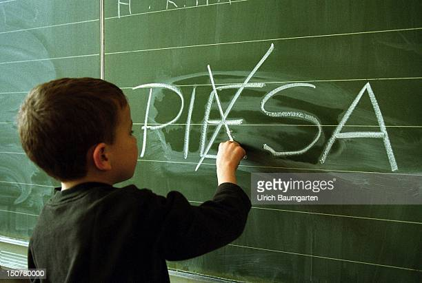 Symbolic photo to the topic PISA study Our photo shows a child which has written ' PIESA ' and is now crossing out the ' E '