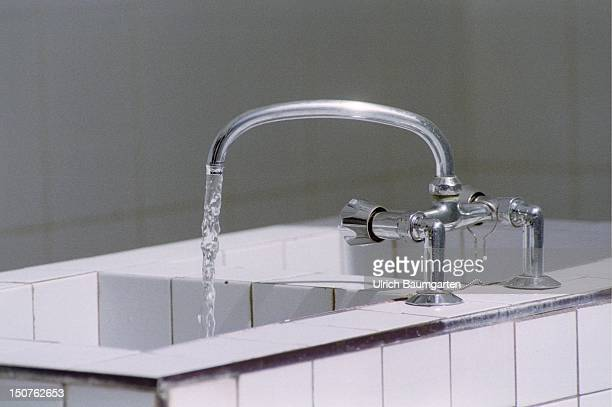 Symbolic photo to the topic water consumption Water running out of a tap into sink tiled with white tiles