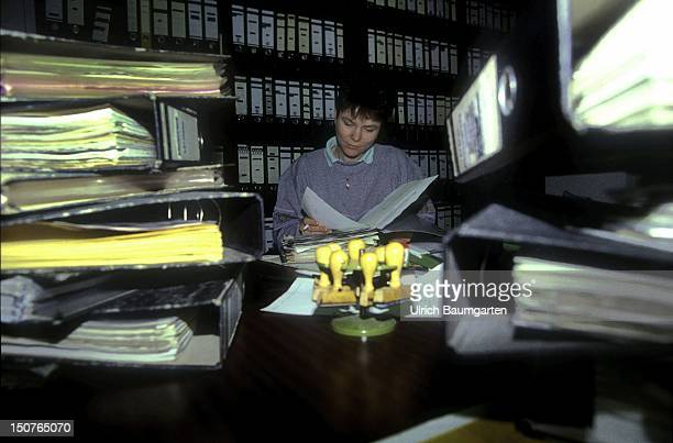 Symbolic photo to the topics Administration office A Woman between files mountains