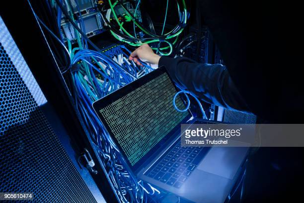 Symbolic photo with topic online crime data theft and piracy A man poses with a laptop showing a binary code in front of Server racks in a server...
