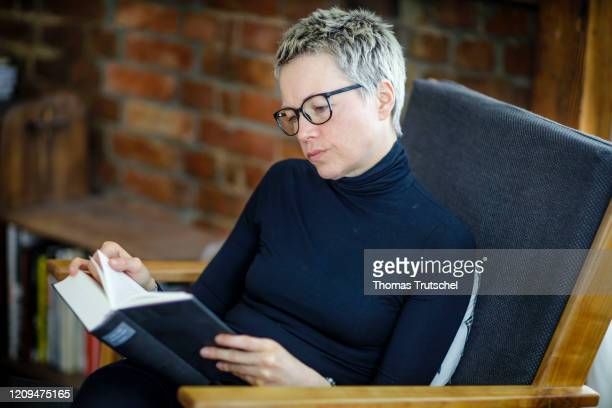 Symbolic photograph A woman sits at home in an armchair and reads a book on April 06 2020 in Berlin Germany