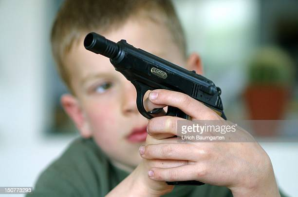 Symbolic picture children and weapons Child with toy pistol in his hands
