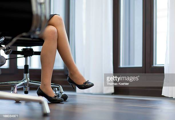 Symbolic picture: Legs of a female manager sitting in a conference room, women's quota.