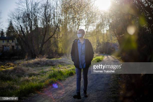 Symbolic picture on the subject of social distancing A woman goes for a walk alone She wears a mouth guard on April 05 2020 in Berlin Germany After...