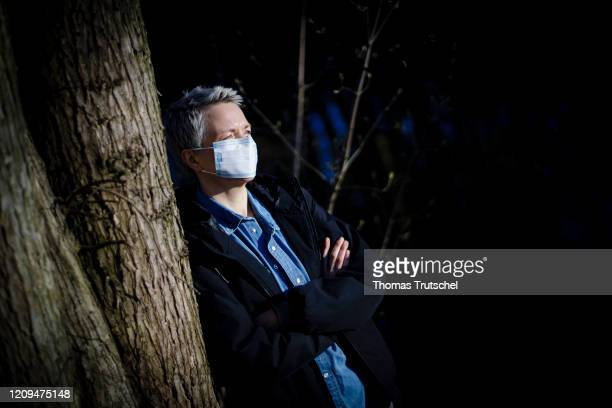 Symbolic picture on the subject of social distancing A woman is leaning against a tree She wears a mouth guard on April 05 2020 in Berlin Germany...