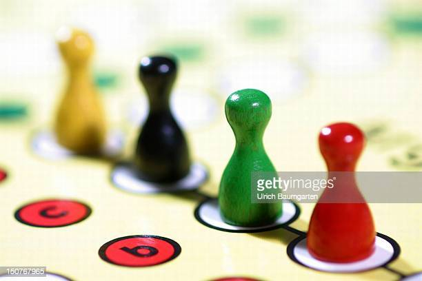 Symbolic picture Politics Parties in Germany Ludo pieces in the colours red green black and yellow on the board