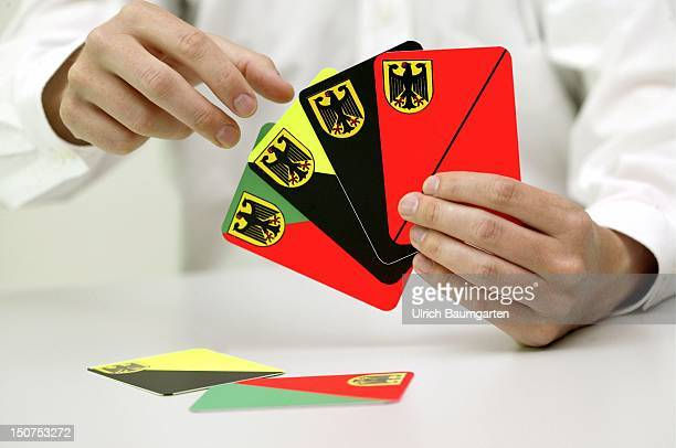 Symbolic picture to the topics: possible coalitions, parties, parliamentary election, Our picture shows a hand holding play card in the colours...