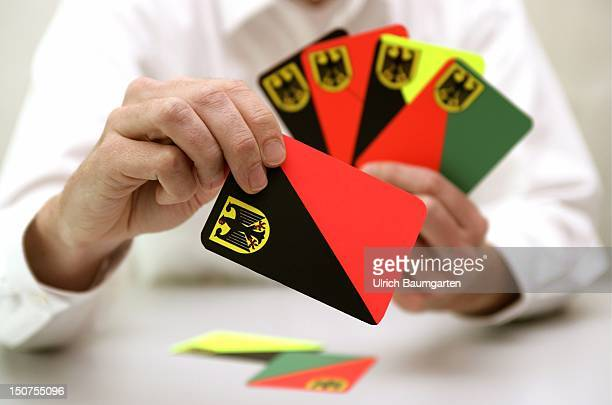 Symbolic picture to the topics possible coalitions parties parliamentary election Our picture shows hand holding play card in the colours black/red...