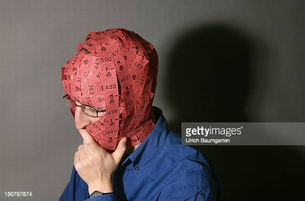 Symbolic picture Unemployment frustration of an unemployed person Head wrapped up in waiting tickets of an unemployment office