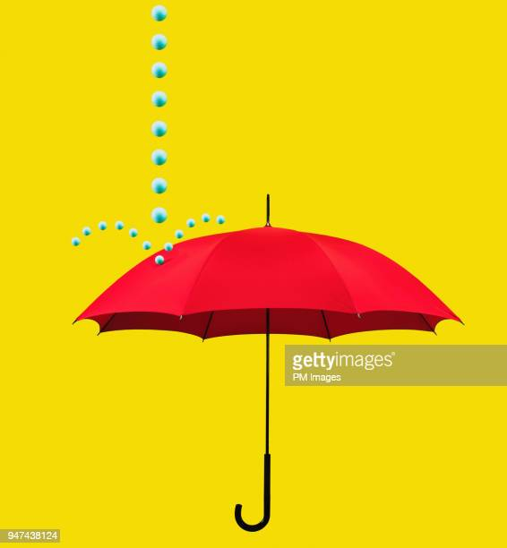 Symbolic rain drops falling on red umbrella