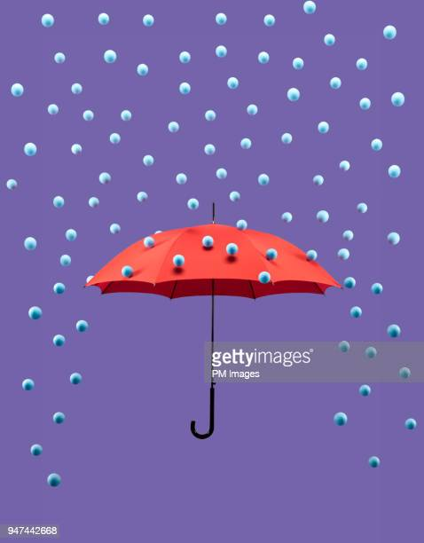 symbolic rain drops falling on red umbrella - protection stock pictures, royalty-free photos & images