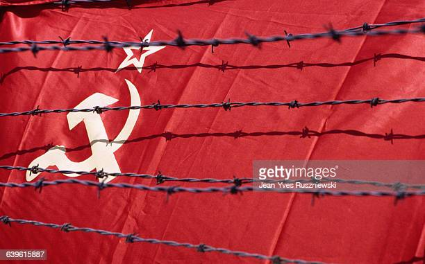 Symbols of the USSR flag the hammer the sickle and the red star behind barbed wire